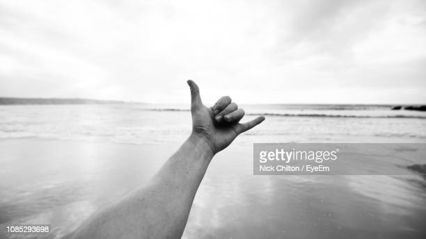 Close-Up Of Hand Showing Shaka Sign Against Beach