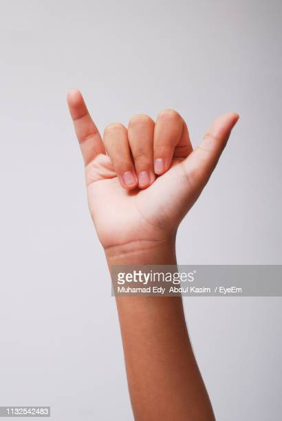 Close-Up Of Hand Sign Against White Background