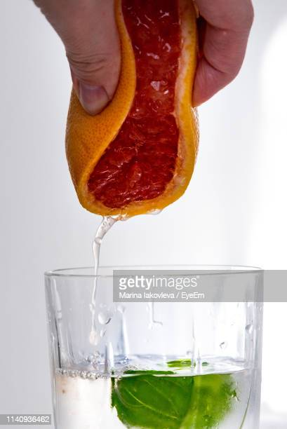 Close-Up Of Hand Squeezing Grapefruit In Glass Over White Background