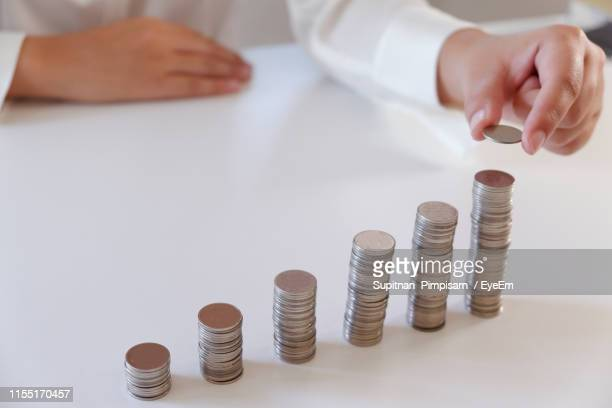 close-up of hand stacking coins on table - putting stock pictures, royalty-free photos & images