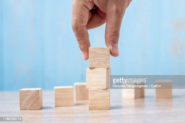 close-up of hand stacking wooden blocks on table - toy block stock pictures, royalty-free photos & images