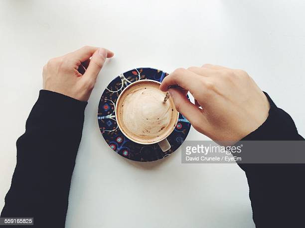 Close-Up Of Hand Stirring Coffee With Spoon Over White Background