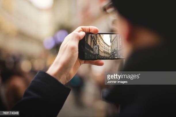 Close-up of hand taking picture of city street