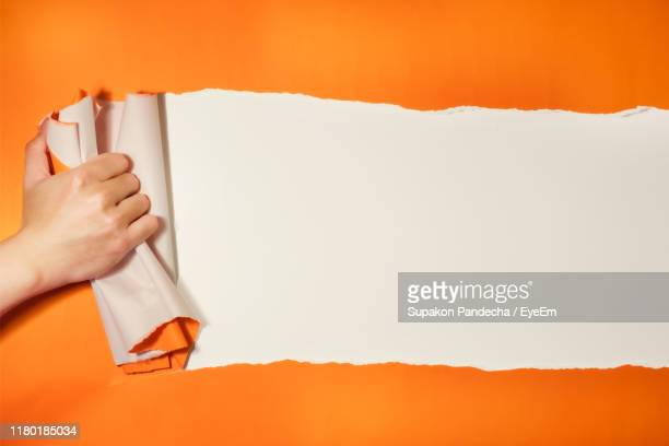 close-up of hand tearing paper - tear stock pictures, royalty-free photos & images
