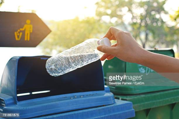 Close-Up Of Hand Throwing Bottle Into Trash Can