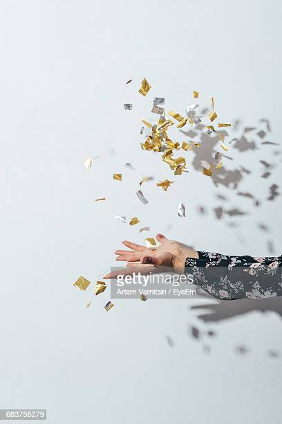 close-up of hand throwing confetti - gold confetti stock photos and pictures
