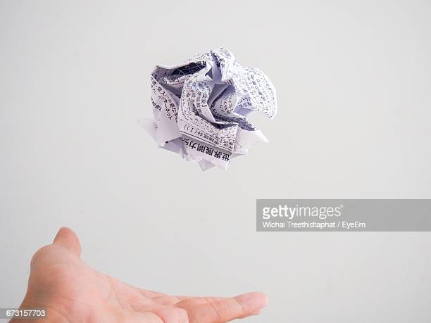 Close-Up Of Hand Throwing Paper Ball
