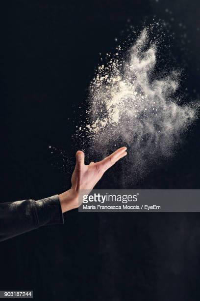 close-up of hand throwing talcum powder against black background - lanciare foto e immagini stock