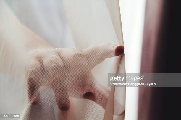 Close-Up Of Hand Touching Curtain