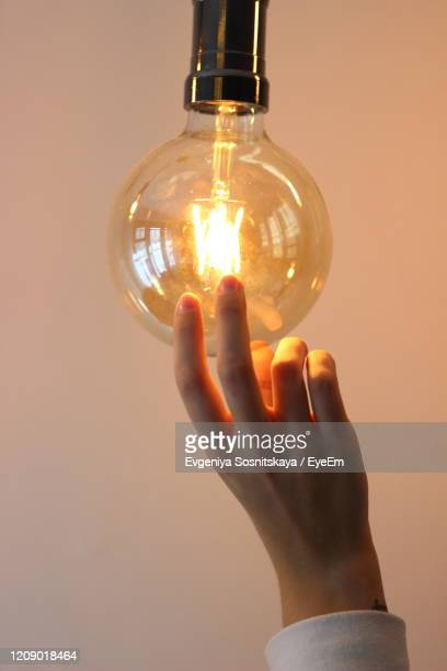close-up of hand touching light bulb - ver através - fotografias e filmes do acervo