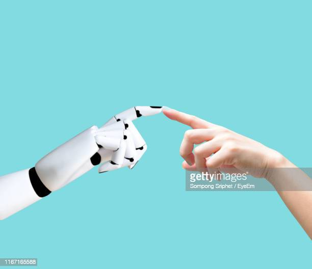 close-up of hand touching robot against turquoise background - people stock pictures, royalty-free photos & images