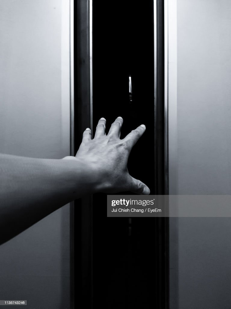 Close-Up Of Hand Touching Window : Stock Photo