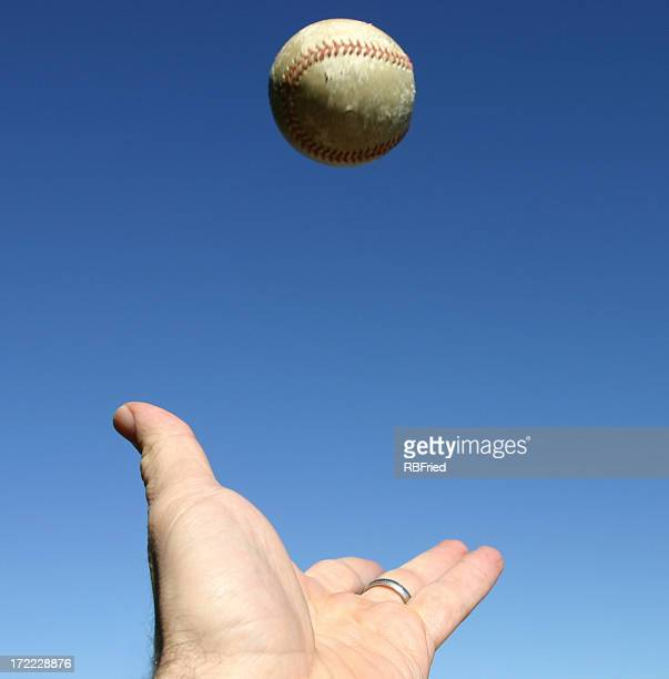 Close-up of hand trying to catch a ball in the sky