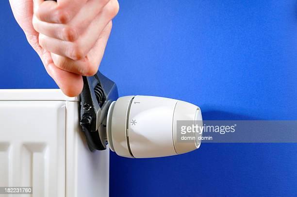 Gros plan de la main d'éteindre thermostat sur blanc Radiateur, clé