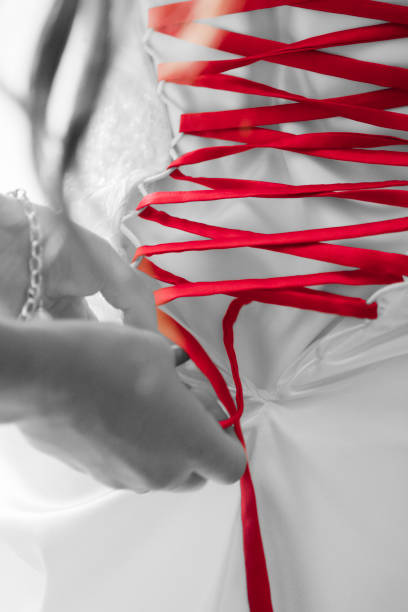 Close-Up Of Hand Tying Red Band On Wedding Dress