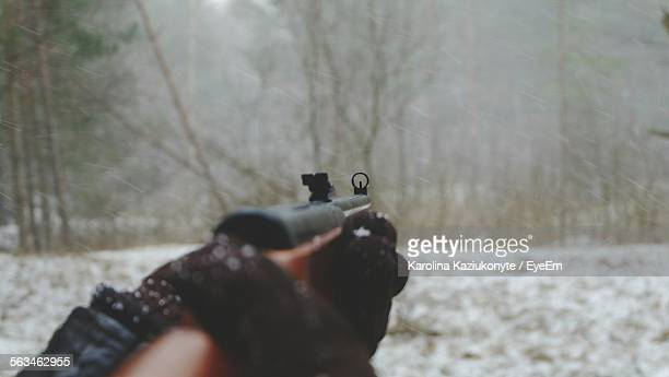 Close-Up Of Hand Using A Gun Against Trees