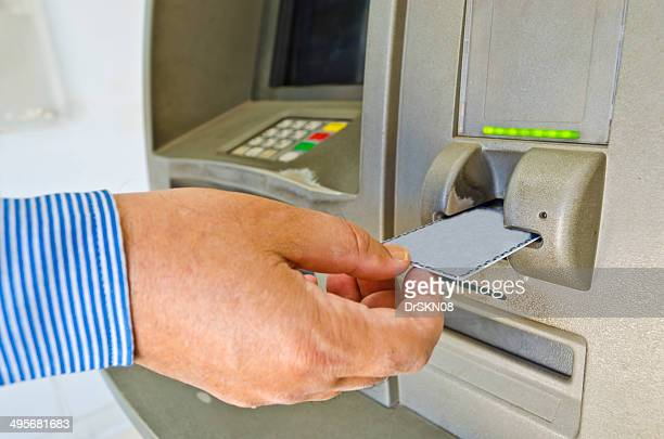 Closeup of hand using ATM card