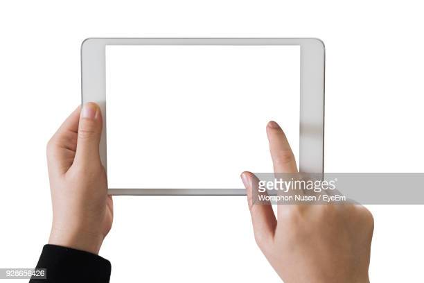 close-up of hand using digital tablet against white background - pc ultramobile foto e immagini stock