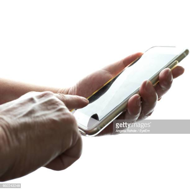 Close-Up Of Hand Using Mobile Phone Against White Background