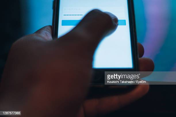 close-up of hand using mobile phone. user typing password for sign in web - koukichi stock pictures, royalty-free photos & images