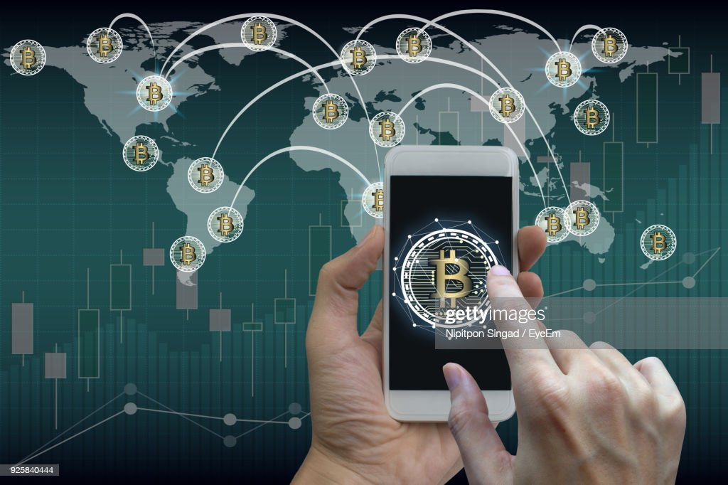 Close-Up Of Hand Using Mobile Phone With Bitcoin Symbol Against World Map : Stock Photo