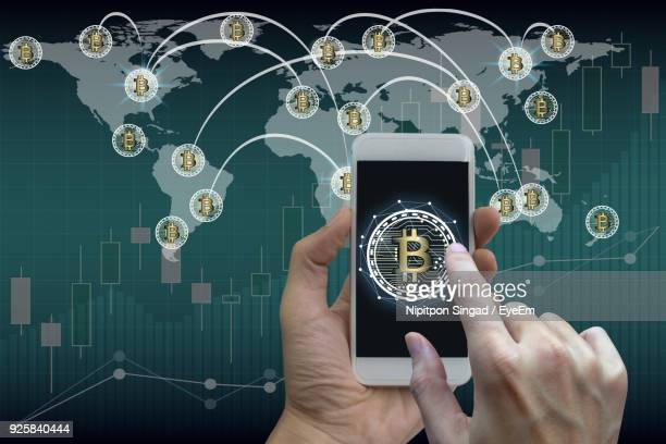 Close-Up Of Hand Using Mobile Phone With Bitcoin Symbol Against World Map