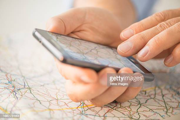 close-up of hand using smartphone over map - gps map stock photos and pictures