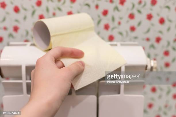 close-up of hand using toilet paper.toilet paper is on a white battery in a weave. - odessa crisis stock pictures, royalty-free photos & images