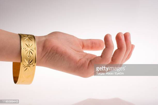 close-up of hand wearing bangle against white background - ブレスレット ストックフォトと画像