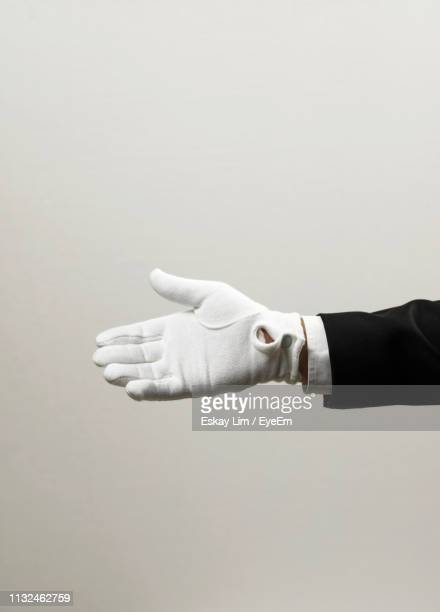 close-up of hand wearing glove against gray background - white glove stock pictures, royalty-free photos & images