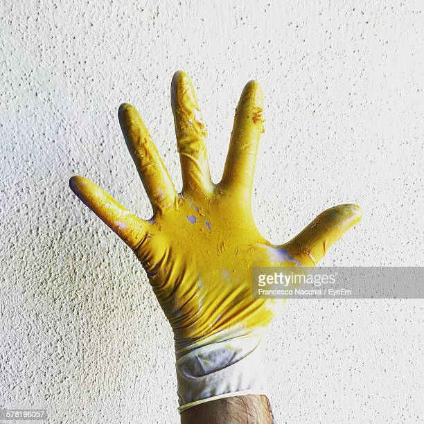 Close-Up Of Hand Wearing Glove With Yellow Paint Against Wall