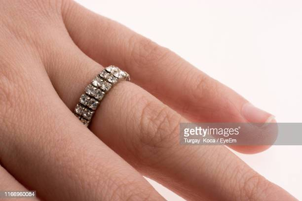 close-up of hand wearing ring against white background - skin diamond stock pictures, royalty-free photos & images