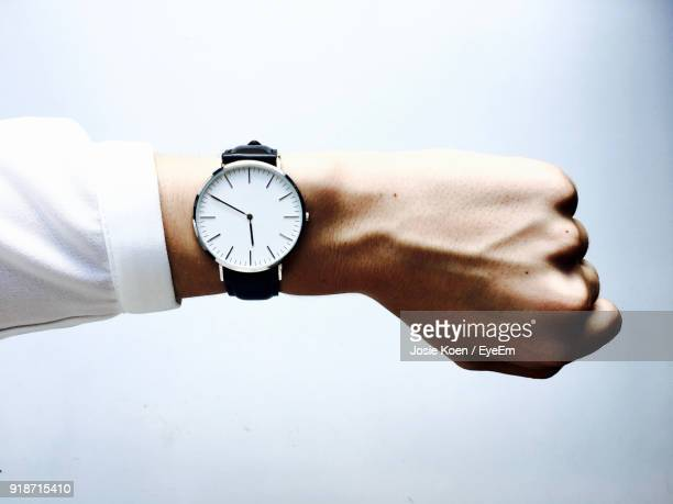 close-up of hand wearing wristwatch against white background - temps qui passe photos et images de collection