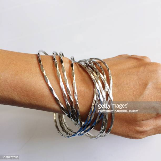 close-up of hand with bangles over white background - バングル ストックフォトと画像