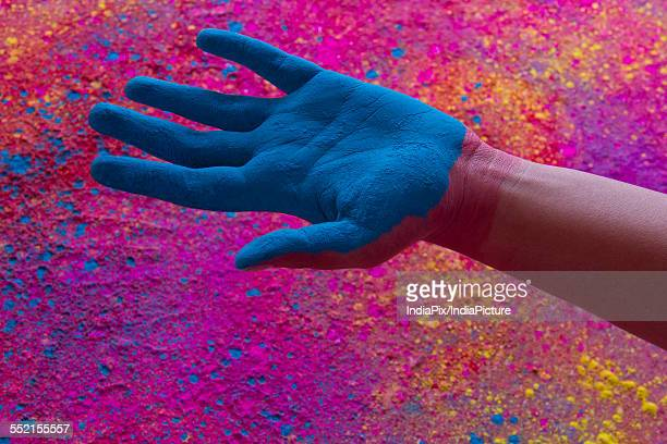 Close-up of hand with blue power paint during Holi festival
