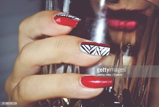 Close-up Of Hand With Nail Art Holding Glass