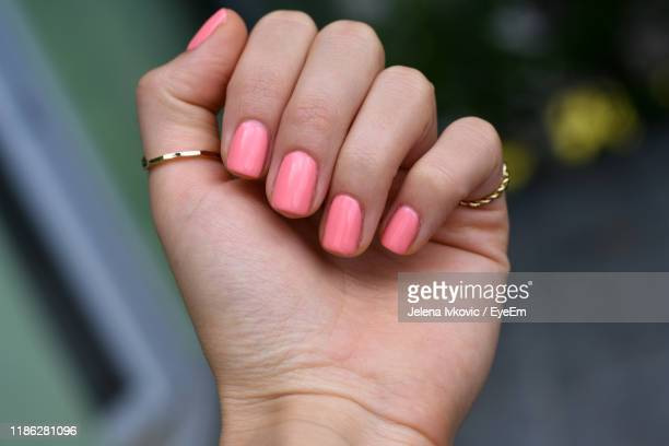 close-up of hand with pink nail polish - jelena ivkovic stock pictures, royalty-free photos & images