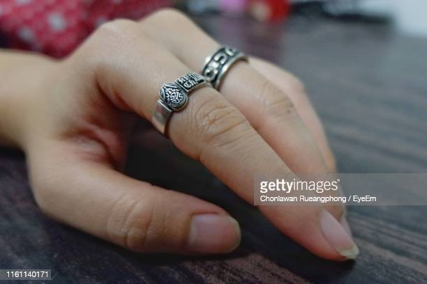 Close-Up Of Hand With Rings On Table