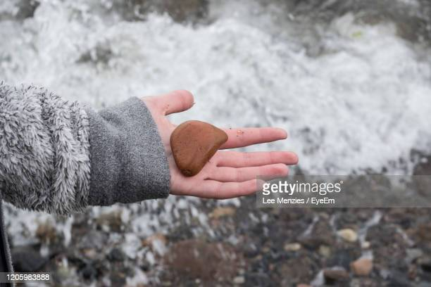 close-up of hand with rock over water - central scotland stock pictures, royalty-free photos & images