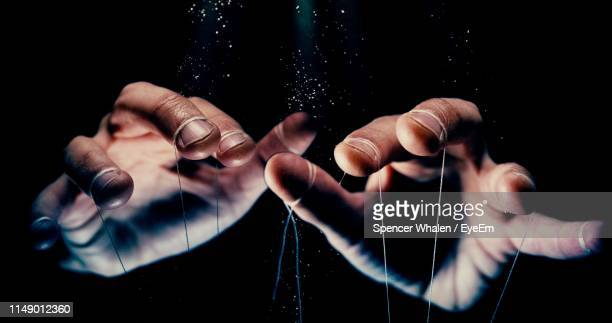 close-up of hand with string against black background - kontrolle stock-fotos und bilder