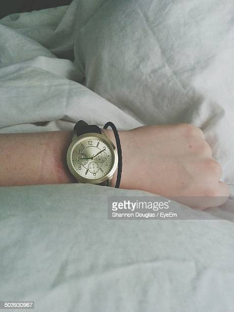 Close-up of hand with wristwatch on bed