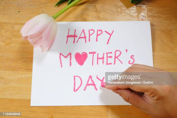 close-up of hand writing happy mothers day on paper - mothers day stock pictures, royalty-free photos & images