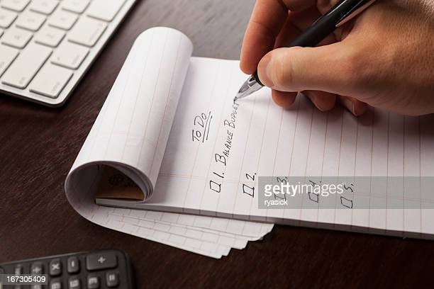 closeup of hand writing in notepad making to do list - list stock pictures, royalty-free photos & images