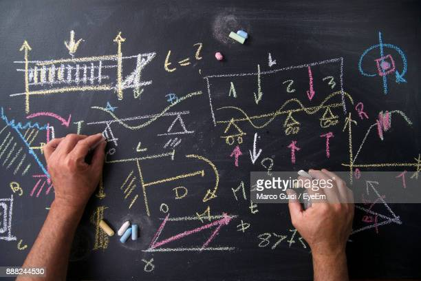 close-up of hand writing with chalk on blackboard - mathematics stock pictures, royalty-free photos & images