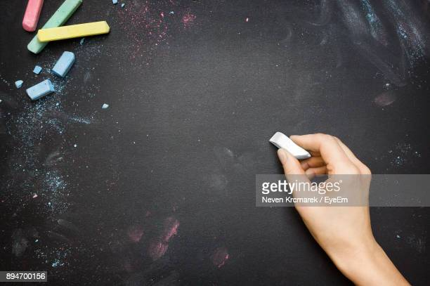 close-up of hand writing with chalk on blackboard - blackboard stock photos and pictures
