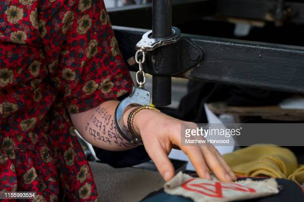 A closeup of handcuffs around the wrist of an Extinction Rebellion protestor who is handcuffed to a boat on Duke Street outside Cardiff Castle as the...