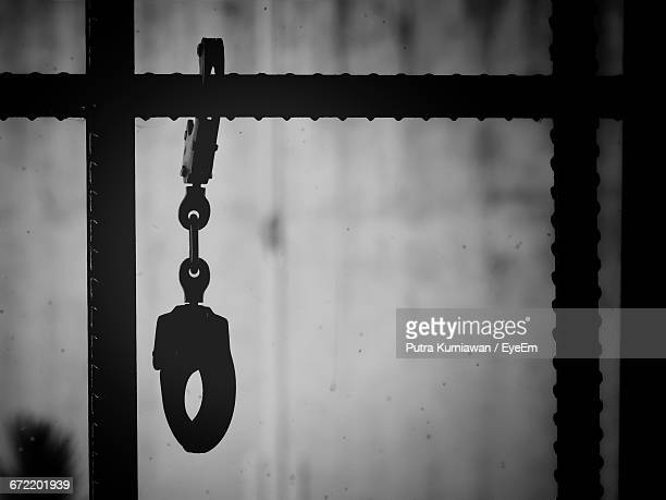 close-up of handcuffs hanging from metal in prison - prison stock pictures, royalty-free photos & images