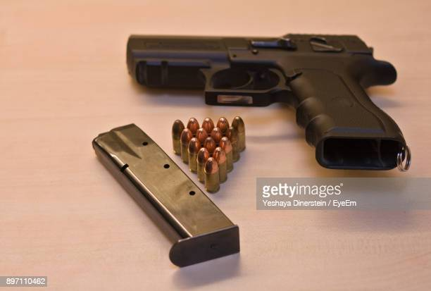 Close-Up Of Handgun And Bullets On Table