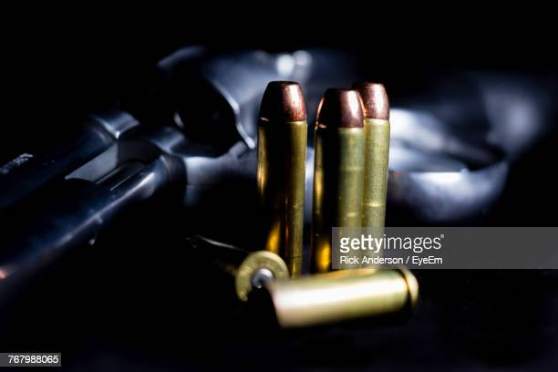 Close-Up Of Handgun And Bullets Over Black Background