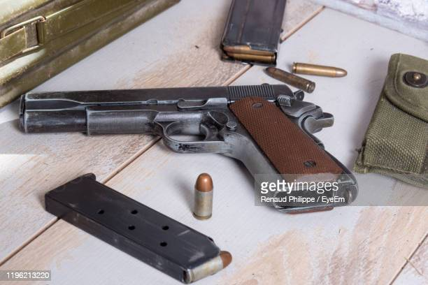 close-up of handgun on table - medium group of objects stock pictures, royalty-free photos & images